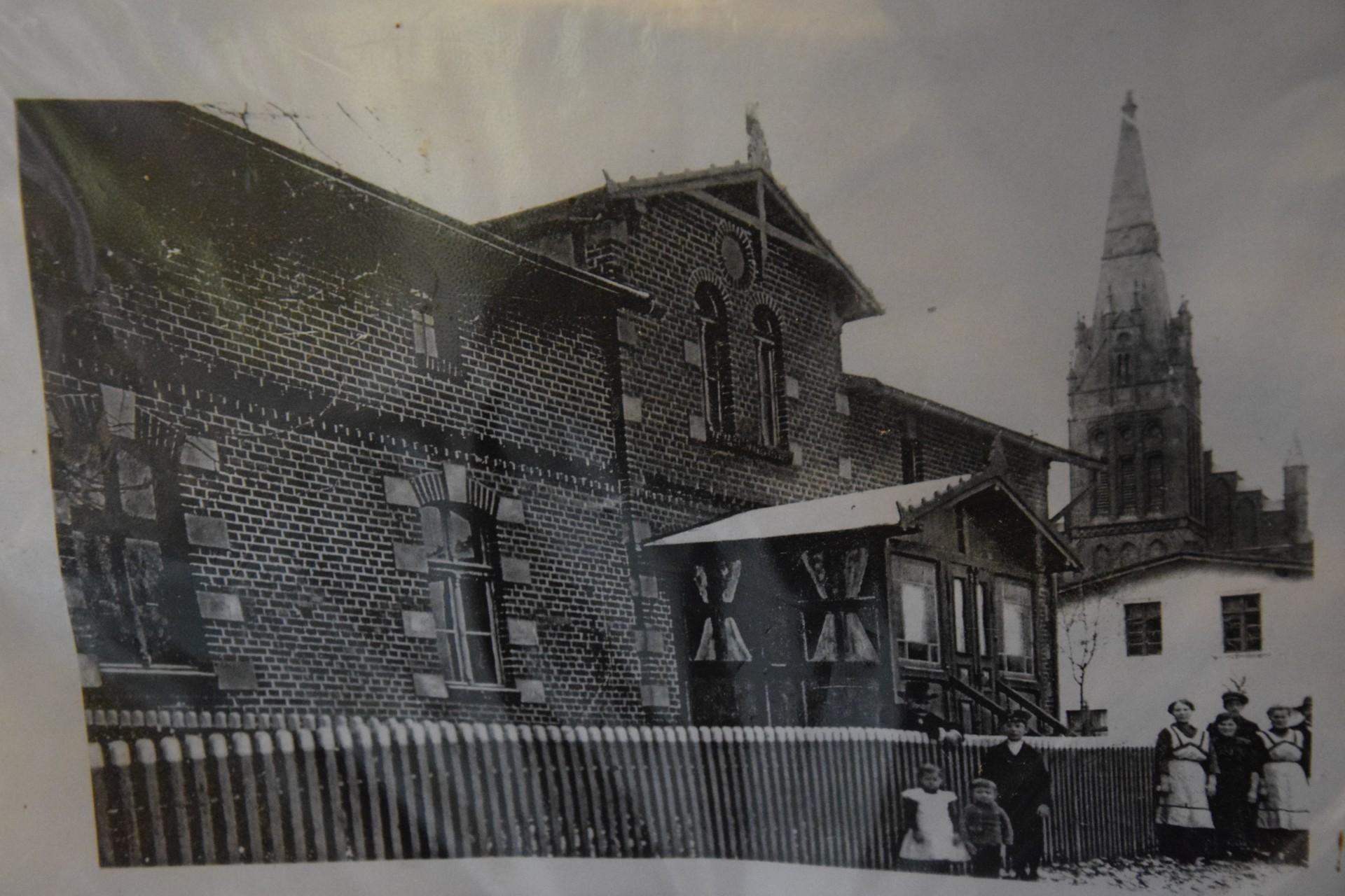 Lipusz. Muzeum Gospodarstwa Wiejskiego. Dom Emila Pircha, w tle - kościół ewangelicki, siedziba dzisiejszego muzeum, jeszcze z wieżą. Źródło: Muzeum Gospodarstwa Wiejskiego w Lipuszu.