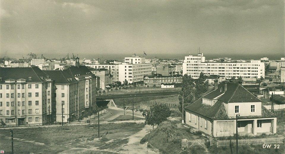 Lata czterdzieste XX wieku. Wybudowane okazałe kamienice stoją jakby... w polu. Miasto wciąż się kształtuje. W prawym dolnym rogu - dom przypominający dworek, nie pasujący do wielkomiejskiej zabudowy.